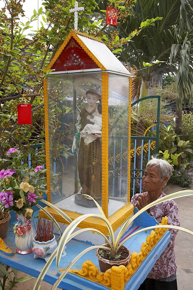 Cambodia woman praying in front of statue in front of a catholic church, at a vietnamese-cambodia community in kampong cham long