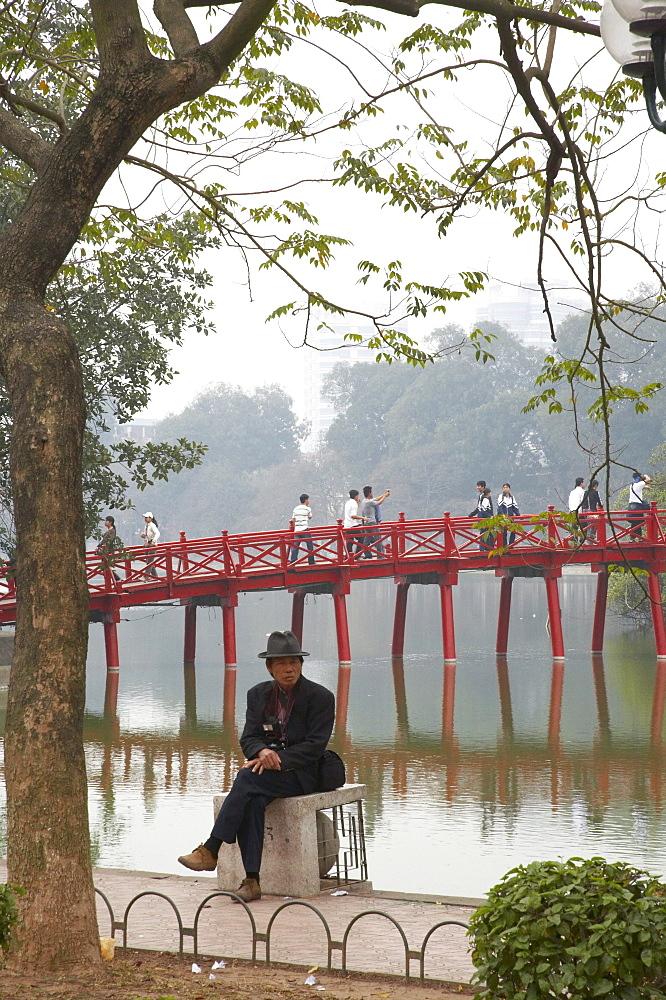 Vietnam people relaxing besdie hoan kiem lake, bridge to ngoc son temple in background, hanoi