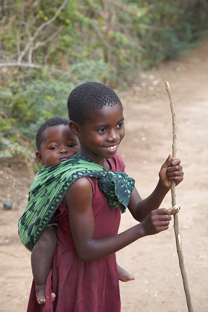 Tanzania small boy being carried by big sister, kalabezo