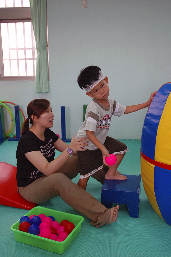 Disability, taiwan. A school for children with special needs, tainan. Boy receiving therapy