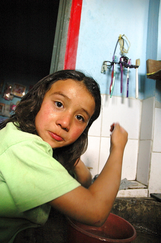 Colombia marly juliet, 7, of the slum of altos de cazuca, bogota, washing her face