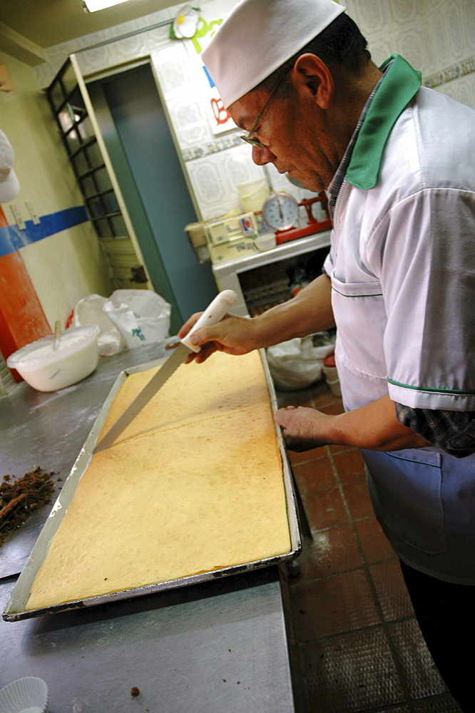 Colombia baker cutting a cake at a bakery in ciudad bolivar, bogota