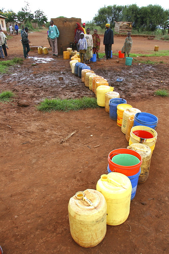 Tanzanian line of buckets waiting to be filled by a slow tap at a water distribution point in kansay, near ngorongoro. They will carry the bucket of water upto 3 miles each way to and from their homes.They And their families suffer from parasites and intestinal complaints because of the contaminated water