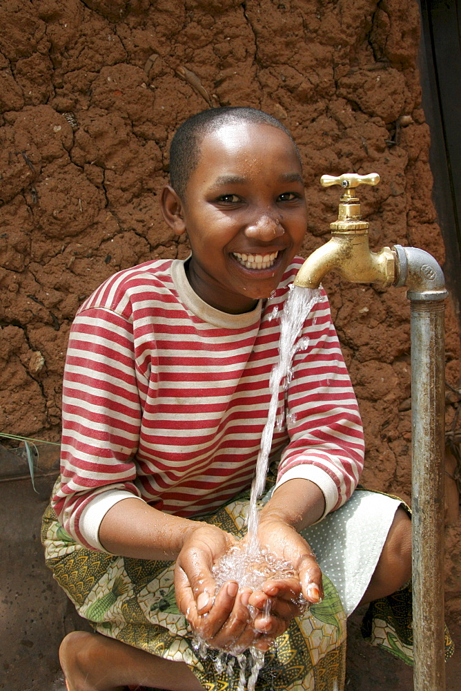 Tanzanian girl taking pleasure at the abundant supply of fresh, safe drinking water which now runs to her house thanks to a development project of caritas tanzania, funded by caritas australia. Mvango village, same, in the north-east near kilimanjaro