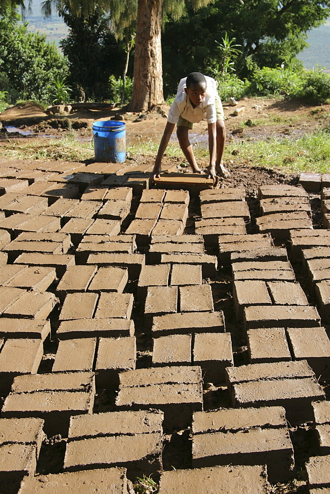 Tanzanian school boy making mud bricks. Kisangara, same, in the north-east near kilimanjaro