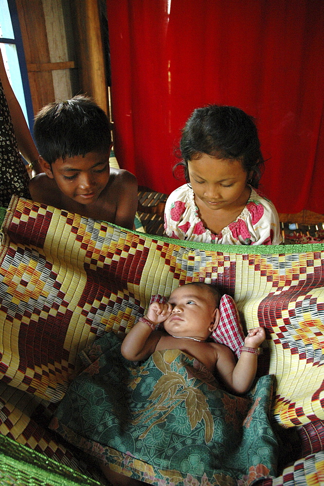 Cambodia girl and boy with their baby brother in hammock. Trac village, kampong cham