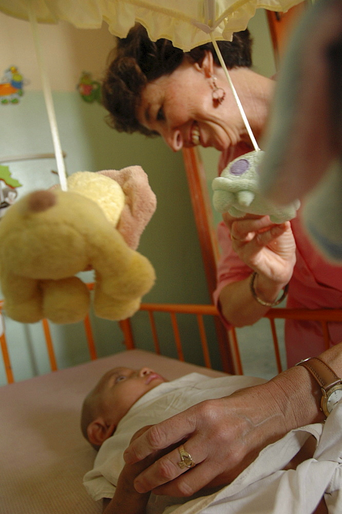 Cambodia american volunteer kathy kremmer taking care of sick babies at an orphanage in pnom penh