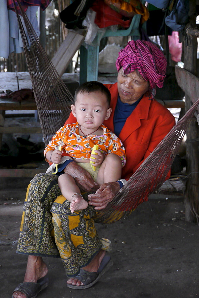 CAMBODIA Grandmother and baby in hammock. Don Tok village, Kampot, lies beside a river estuary and is often flooded by sea water, a consequence of climate change during the last few years. CRS is studying the problem through its partner agency, SCW (Save Cambodian Wildlife). These people have to endure the inconvenience of daily flooding around their homes. photo by Sean Sprague