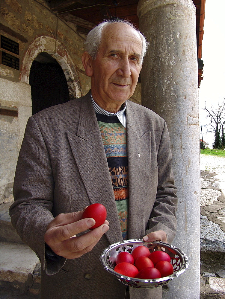 Macedonia (the former yugoslav republic of macedonia, fyrm) man holding easter eggs dyed red, to represent the blood of christ. Saint clement church, ohrid