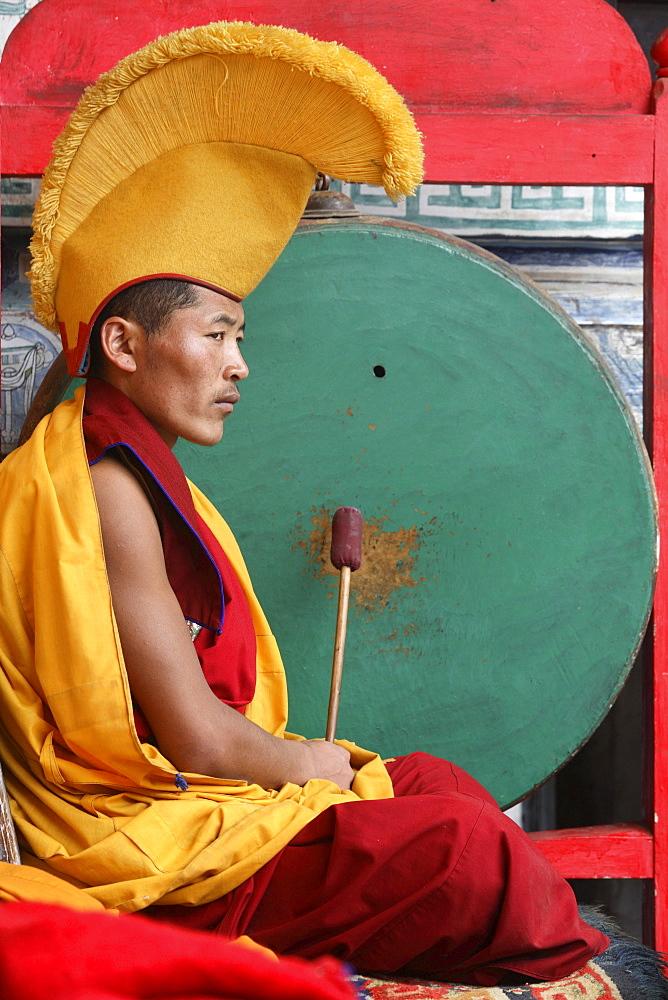 Monk beating traditional drum called gong, int he courtyard of chiwang monastery during mani rimdu festival. chiwang monastery, solu khumbu, nepal