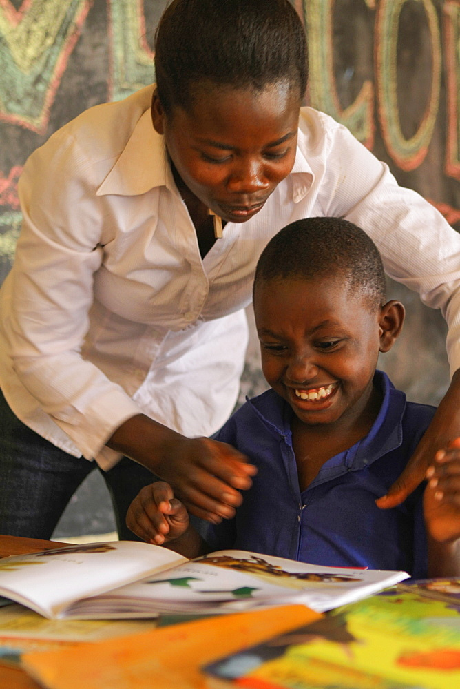 Isingizwe Alice, 8 years old, who is dumb and her teacher Musabyemariya Alphonsine from Ngwino Nawe, teaching Alice how to read a book using signs, Rwanda, Africa