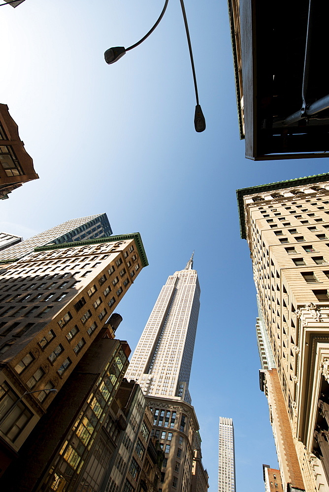 Looking up through skyscrapers at the Empire State, New York, United States of America, North America