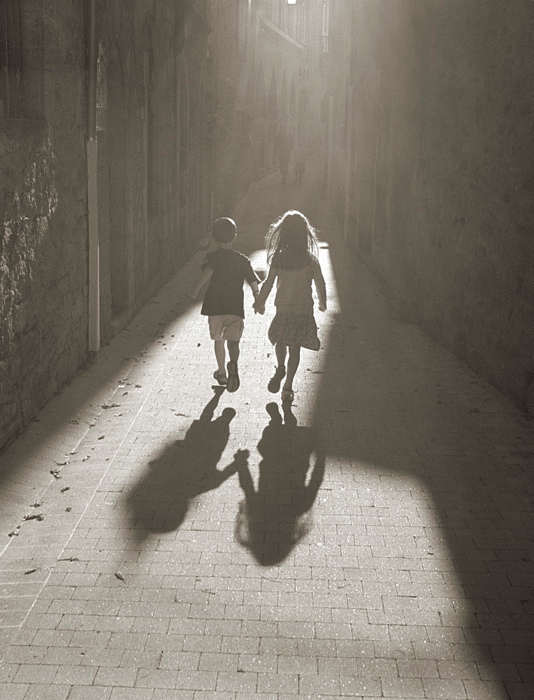 Two children running hand in hand down a sunlit alley, France, Europe