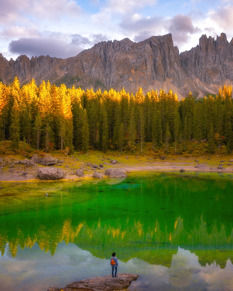 Young man observing the beauty of Lago Di Carezza at sunset, Dolomites, Italy, Europe
