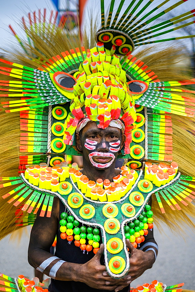 A participant in the Ati-atihan festival wearing brighly-colored hand made costume, Kalibo, Aklan, Western Visayas, Philippines, Southeast Asia, Asia