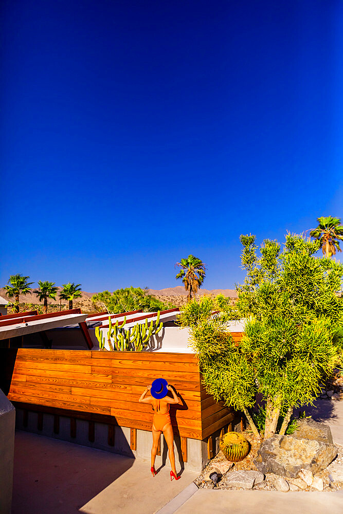 View of beautiful desert home and woman getting a tan. - 1218-1379