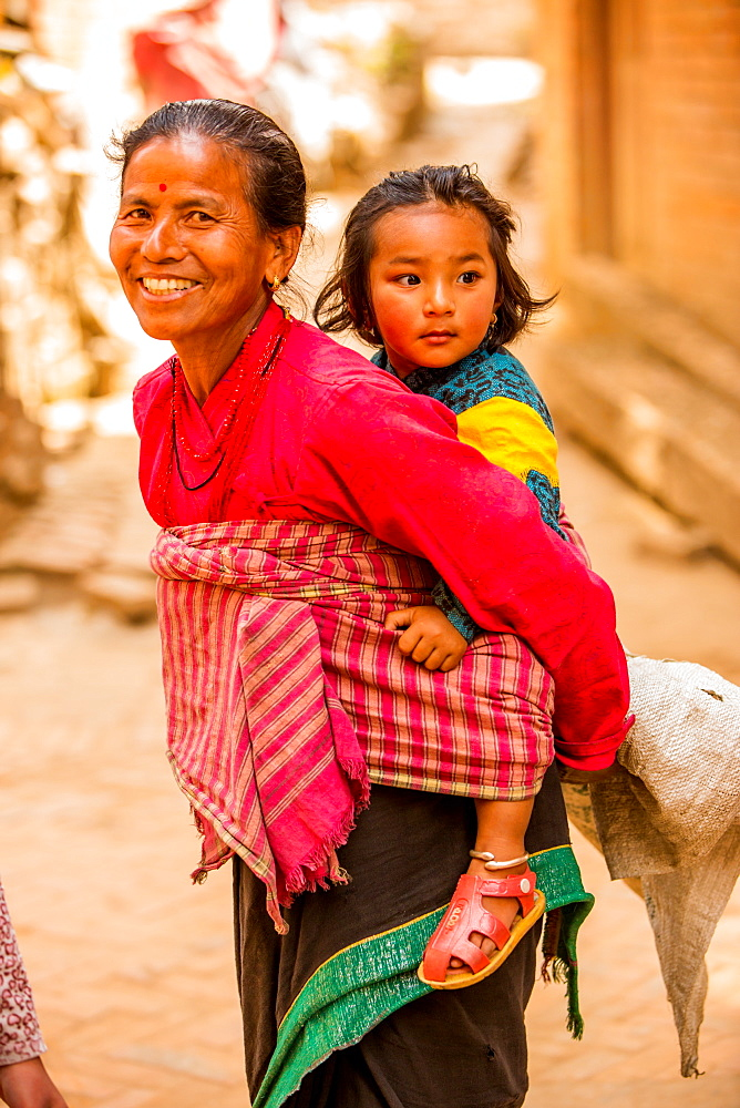 Woman carrying her child in Bhaktapur, Kathmandu, Nepal, Asia
