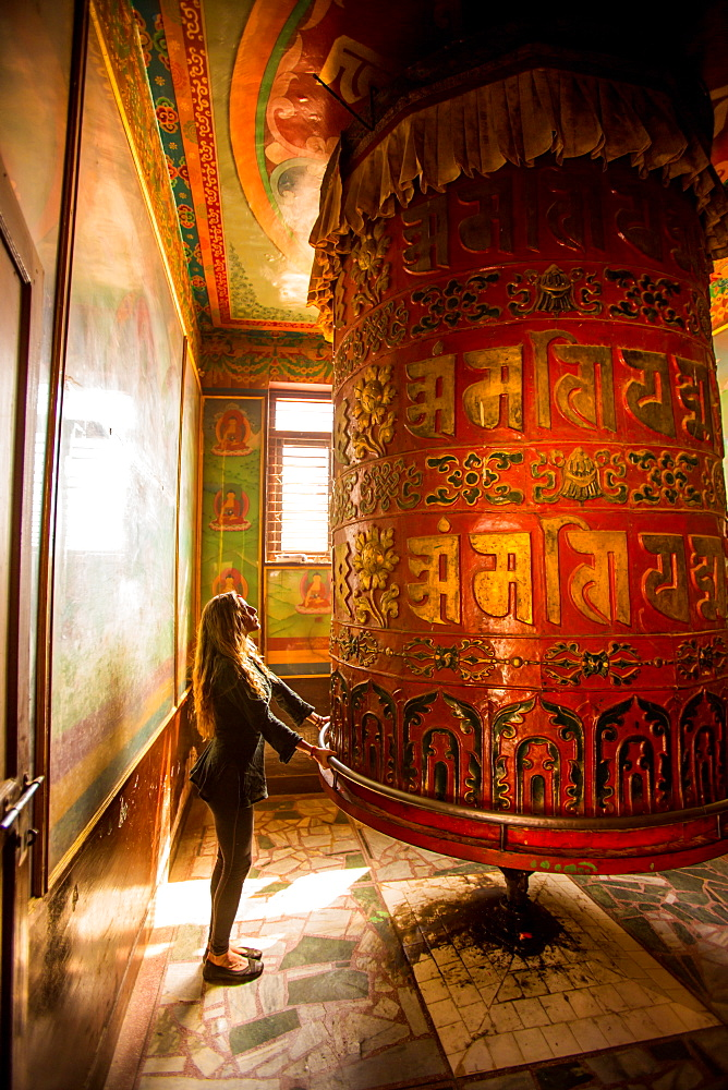 Woman praying at a Buddhist prayer wheel in Bouddha (Boudhanath) temple, UNESCO World Heritage Site, Kathmandu, Nepal, Asia