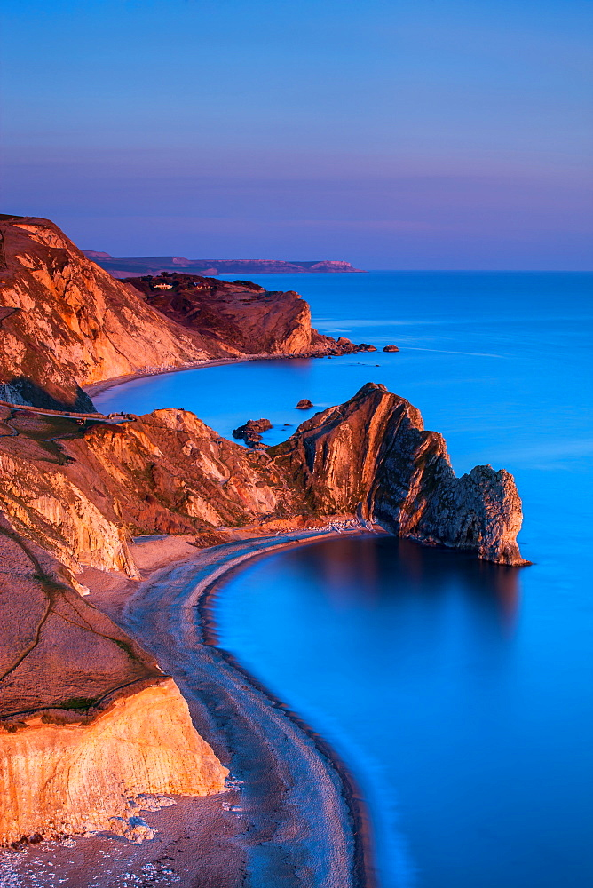 The limestone arch of Durdle Door and St. Oswald's Bay extending along the Jurassic Coast at dusk, UNESCO World Heritage Site, Dorset, England, United Kingdom, Europe