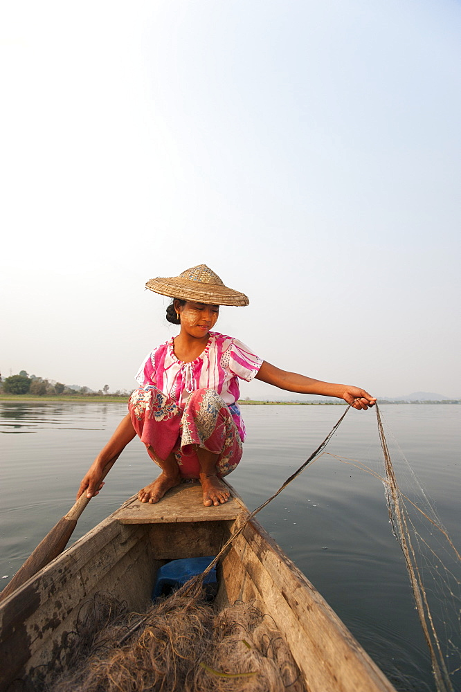 A young woman pulls in her nets at the end of the day on Indawgyi Lake, Kachin State, Myanmar (Burma), Asia - 1225-1155