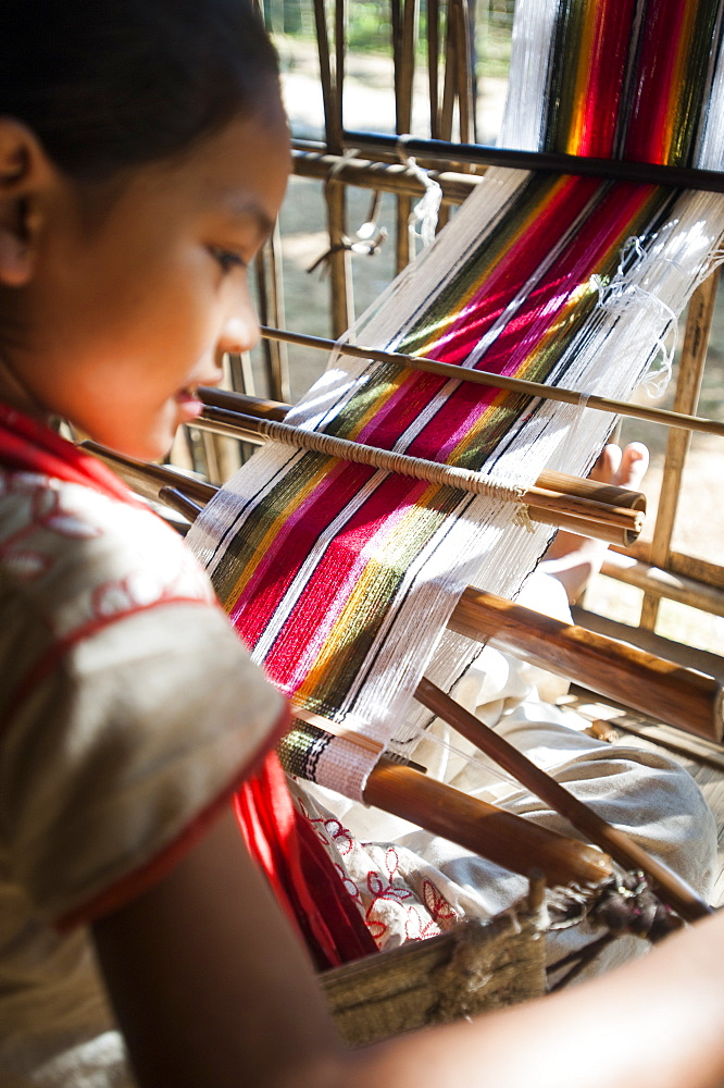 A little girl learns the art of weaving on a hand loom, Chittangong Hill Tracts region, Bangladesh, Asia