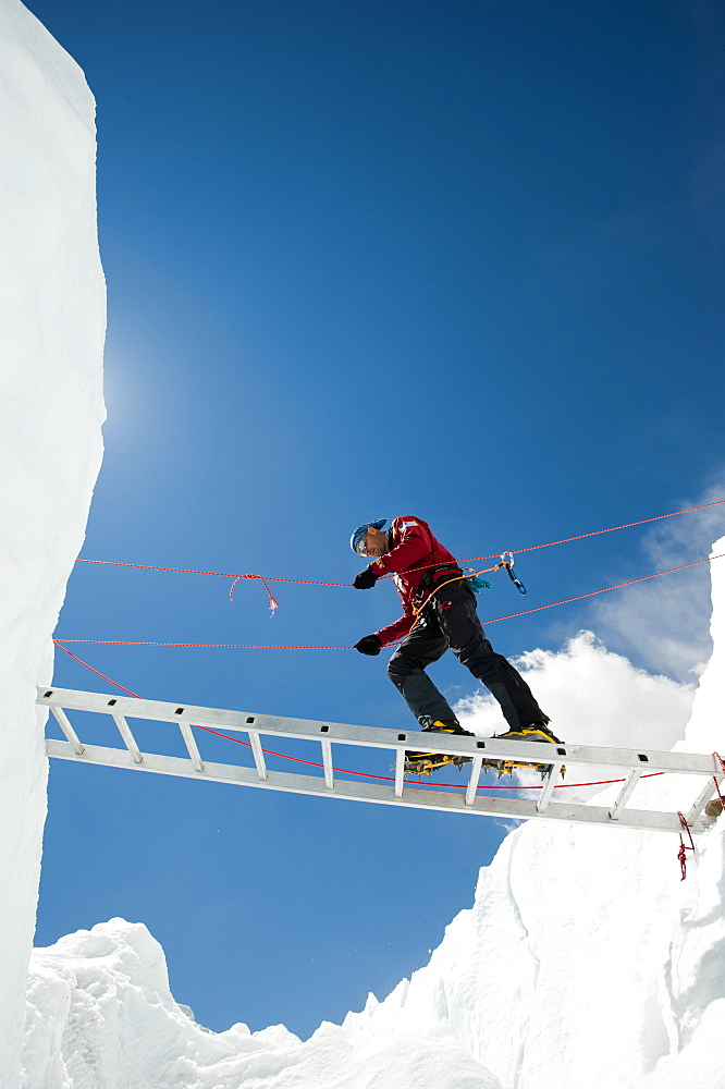 A climber makes his way across a crevasse using a temporary ladder, Khumbu region, Himalayas, Nepal, Asia