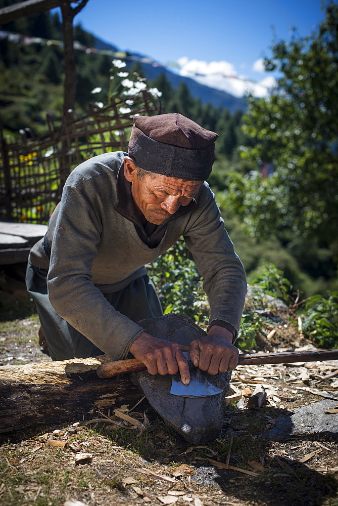 A Tamang man in the Tamang Heritage region close to Langtang sharpens an axe in the traditional way, Langtang Region, Himalayas, Nepal, Asia
