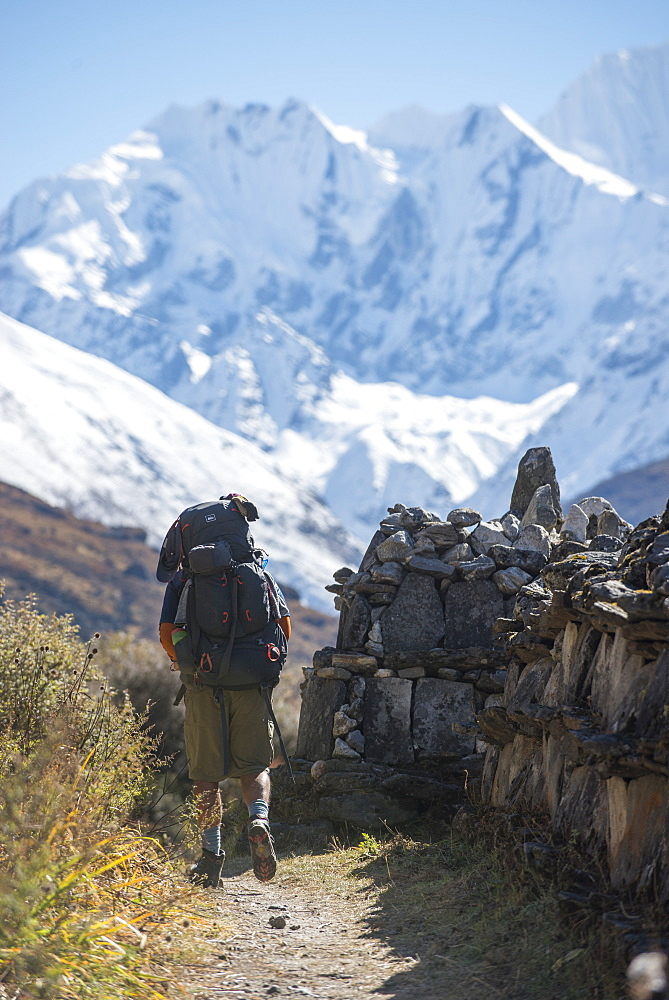 Hiking past a traditional Mani stone wall in the Langtang valley in Nepal with views of Ganchempo in the distance