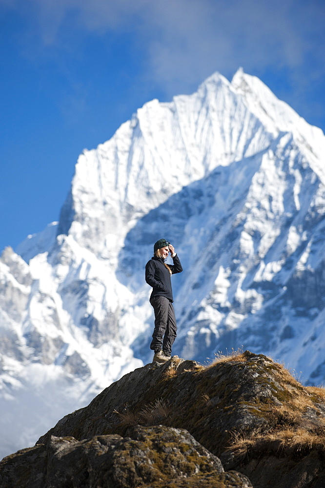A trekker enjoys the views above Namche in the Everest region with views of Thermserku in the distance, Himalayas, Nepal, Asia