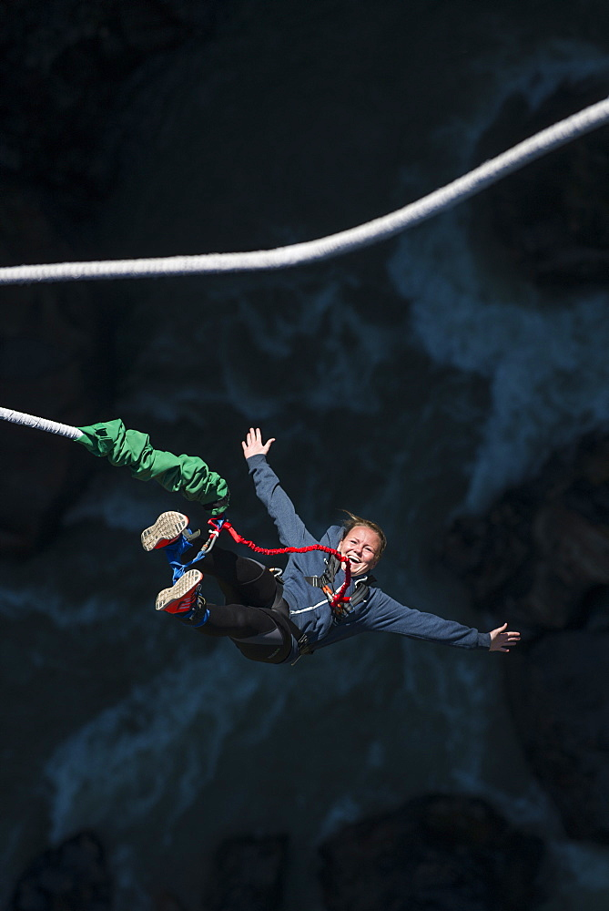 A woman smiles for the camera as she is bounced back up during a Bungee jump at The Last Resort, Nepal, Asia