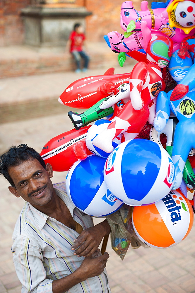 A man selling inflatable toys in Patan, a historical part of Kathmandu, Nepal, Asia