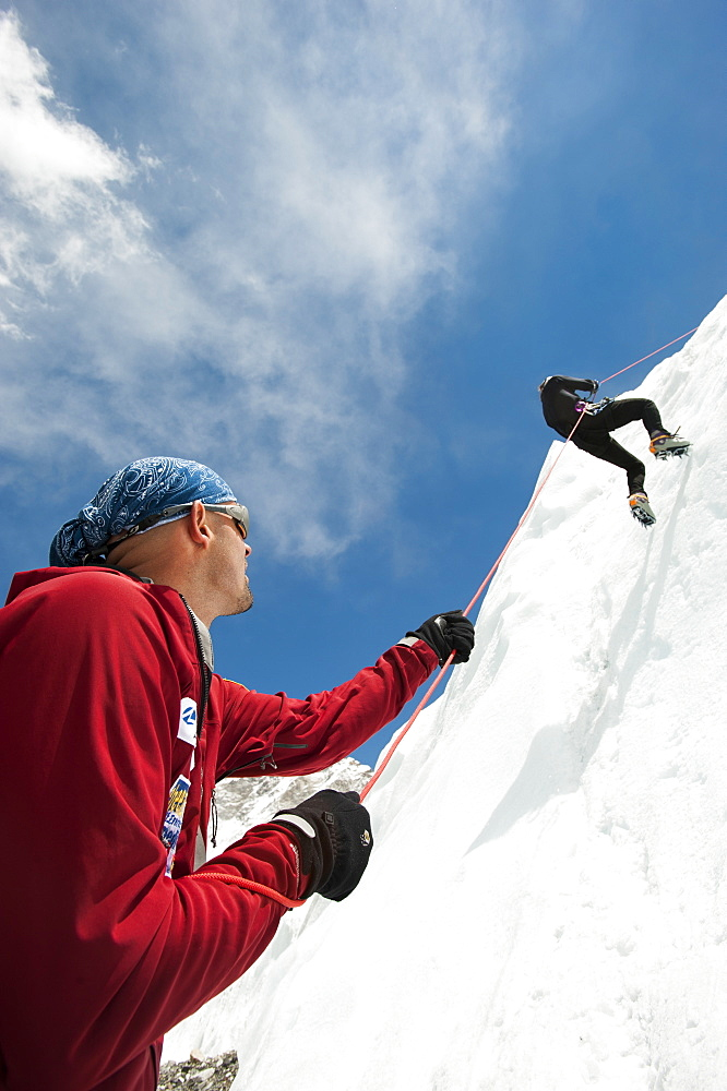 A climber makes her way down an ice wall in preperation for climbing Everest in Nepal