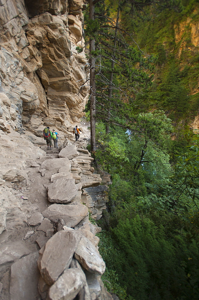 A trekking group makes their way into Dolpa beside the Suli Gadd between Chhepka and Amchi Hospital. Dolpa is a remote and littl