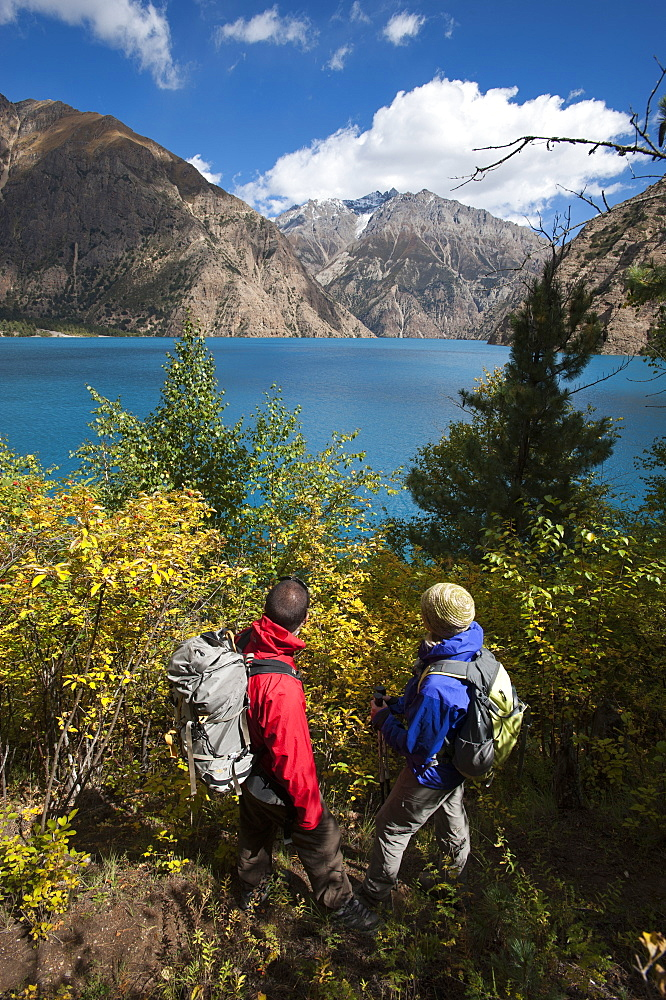 Trekkers look out at the turquoise blue Phoksundo lake in Dolpa in Nepal