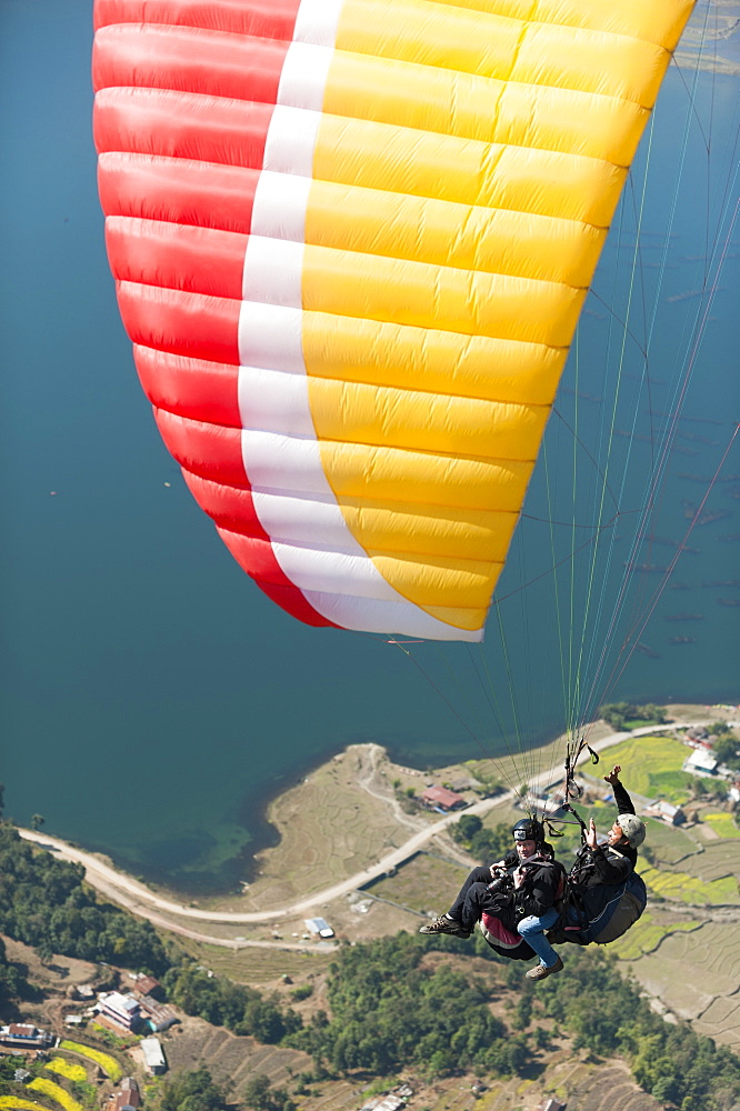 Paragliders make their way to the landing zone next to Phewa Lake, Nepal, Asia