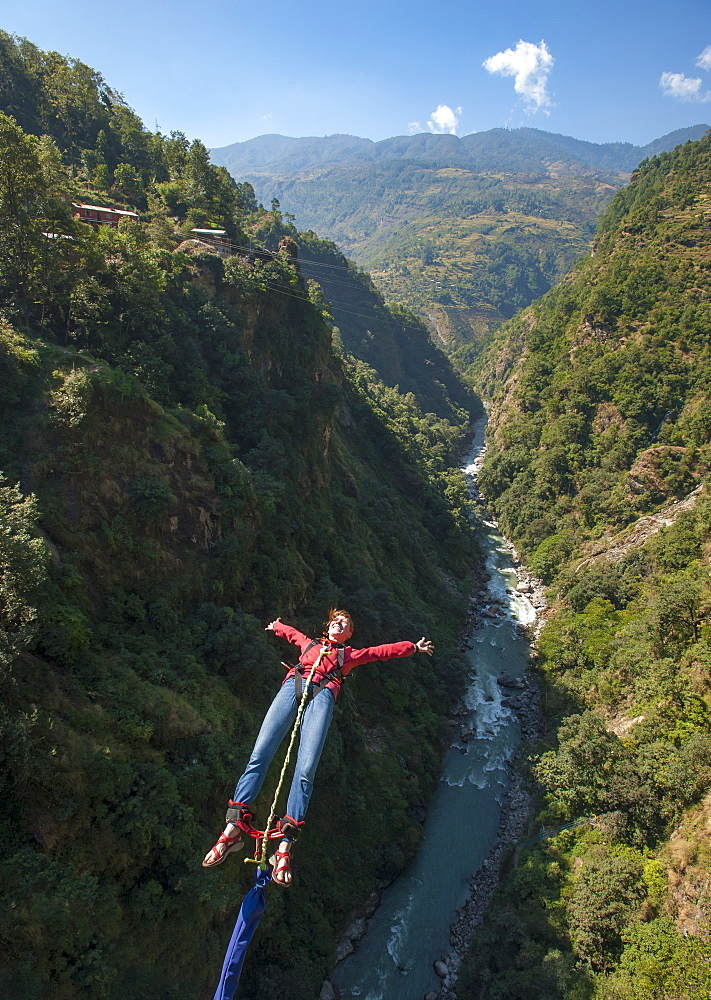 A girl jumps a bungy backwards, Nepal, Asia