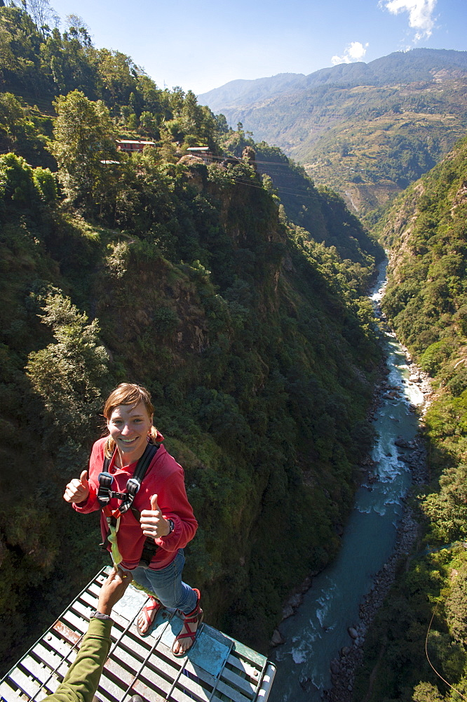 Standing on then edge, a girl prepares herself to take a bungy jump backwards, Nepal, Asia