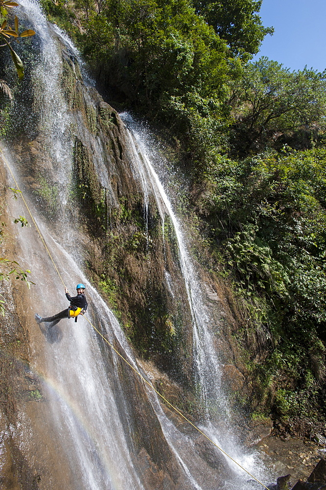 A girl pauses to smile for the camera while canyoning in a waterfall, Nepal, Asia