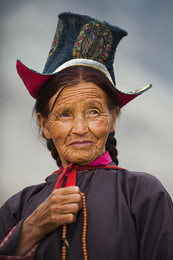 Buddhist woman travelling to a festival at the 14th-century Diskit Monastery, Ladakh, India, Asia