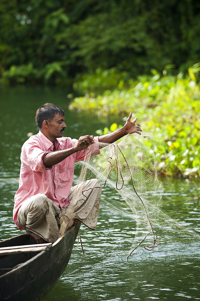A man pulls in his fishing net on Kaptai Lake, Chittagong Hill Tracts, Bangladesh, Asia