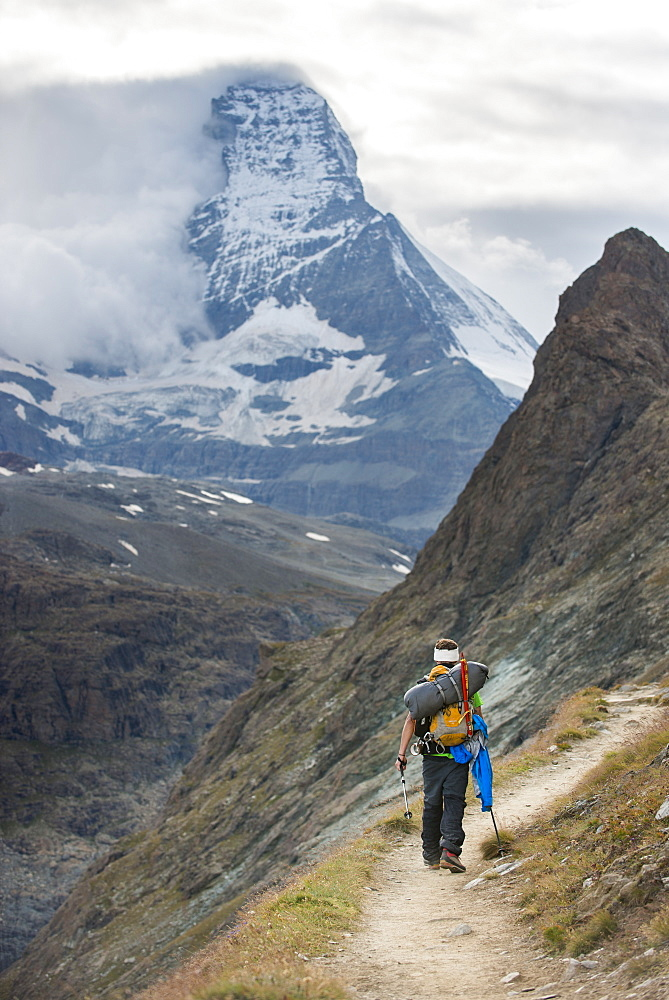 Hiking a trail in the Swiss Alps near Zermatt with a view of The Matterhorn in the distance