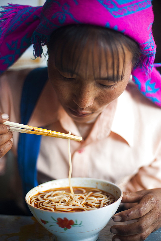 A Miao woman eats a bowl of noodles in Yunnan Province, China, Asia