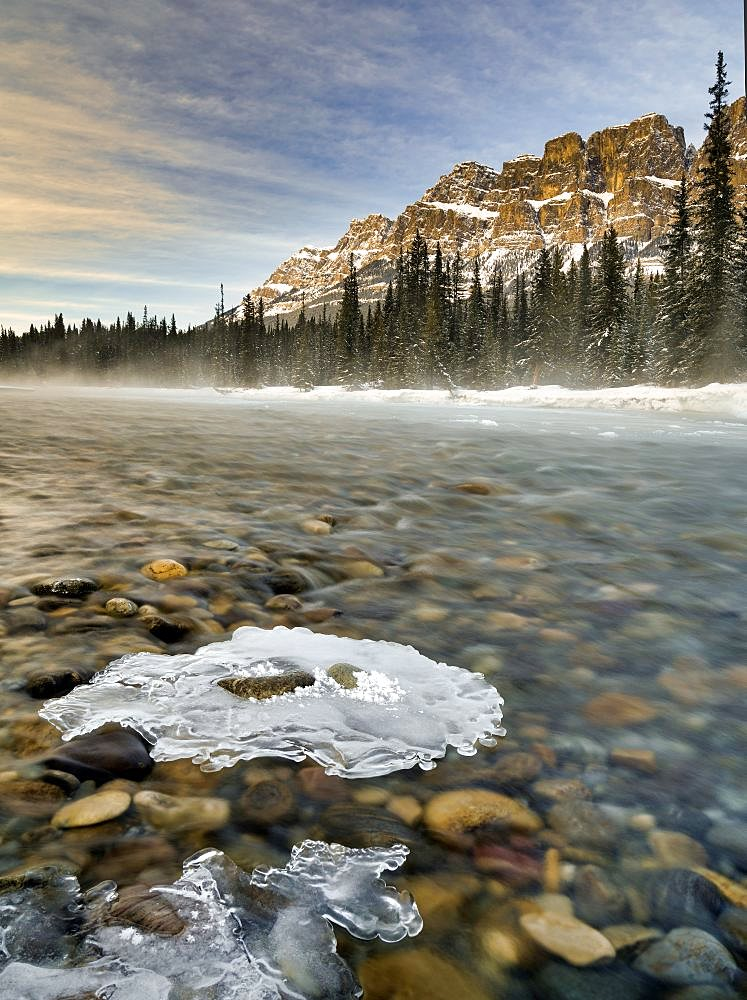 Ice formations on the Bow River and Castle Mountain at sunset Alberta Canada.