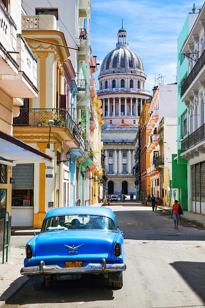 A classic car parked on the street next to colonial buildings with the former Parliament Building in the background, Havana, Cuba, West Indies, Caribbean, Central America - 1231-4