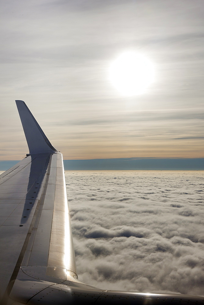 Plane wing with low lying clouds and sunburst, United Kingdom, Europe