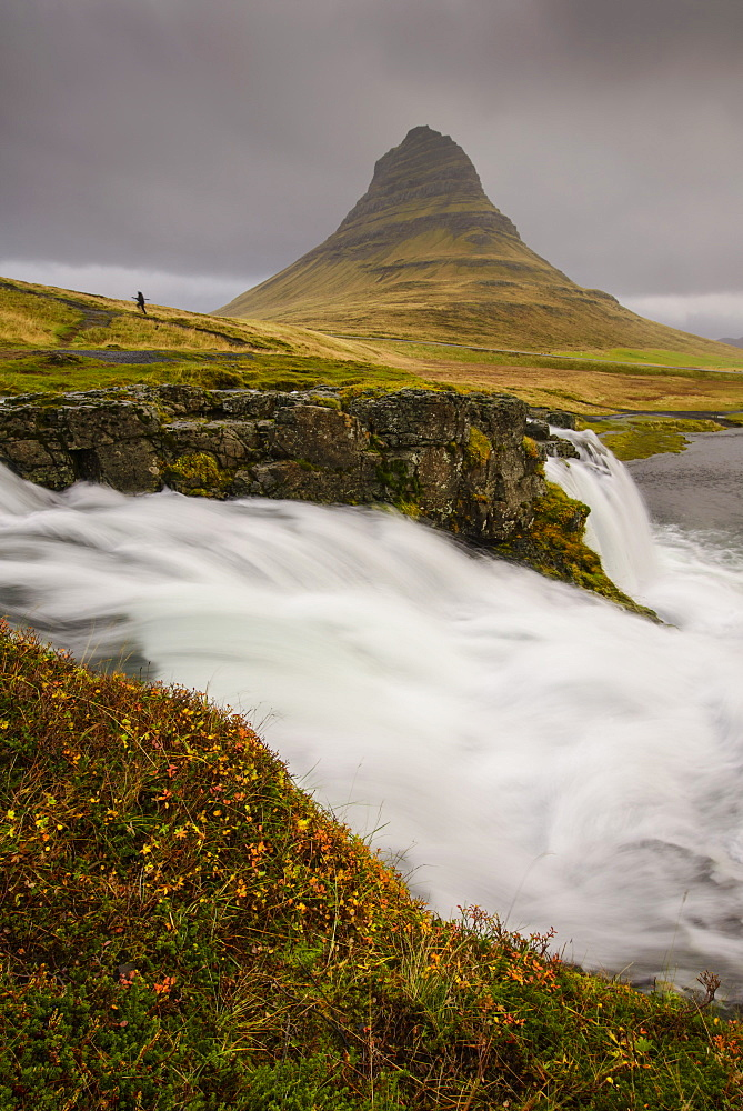 Kirkjufellsfoss in autumn with hiker to show scale, Iceland, Polar Regions