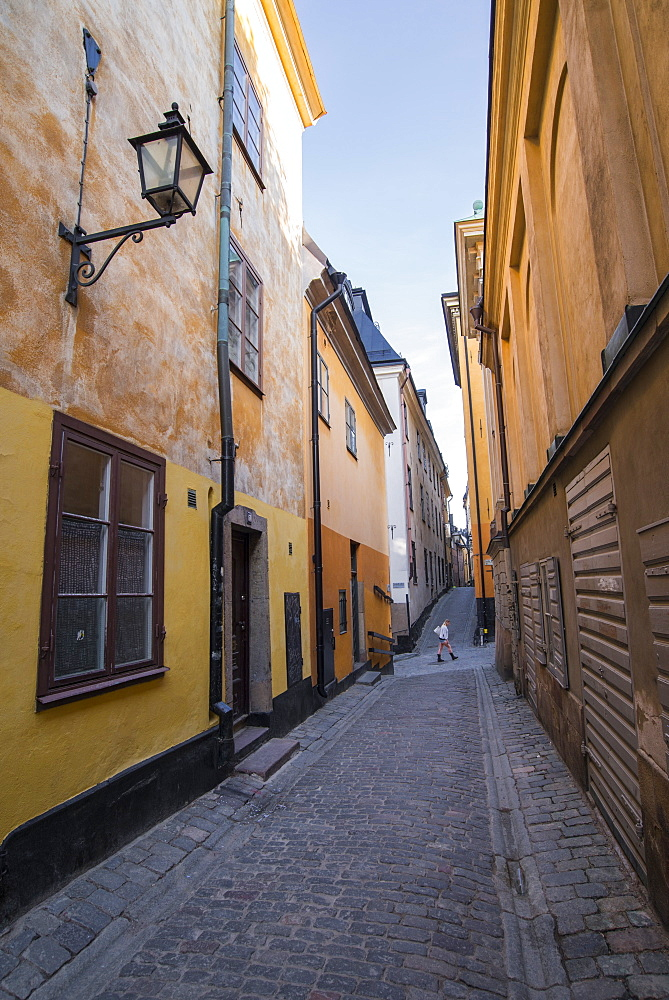 A pedestrian walks the streets of Stockholm's colorful and historic Gamla Stan district, Stockholm, Sweden, Scandinavia, Europe