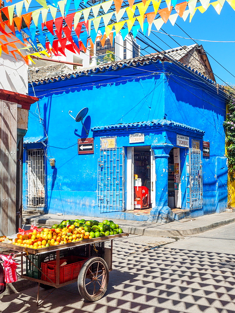 Colorful flags, blue building, and fruit cart on a street corner in Getsemani barrio, Cartagena, Colombia, South America