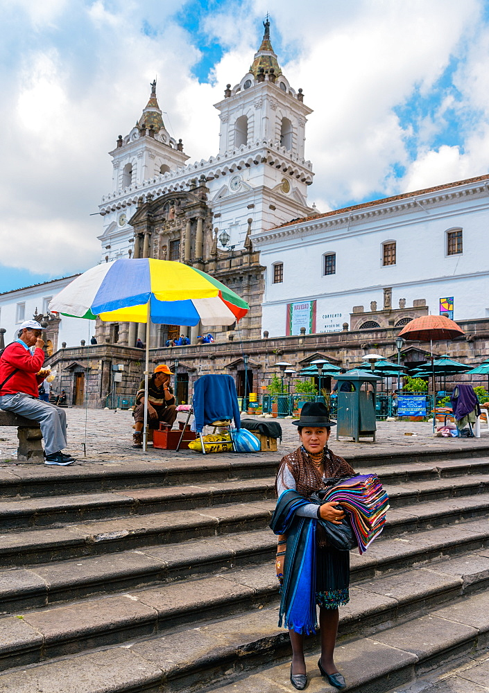 A traditionally dressed indigenous woman sells textiles in central Quito, Ecuador, South America