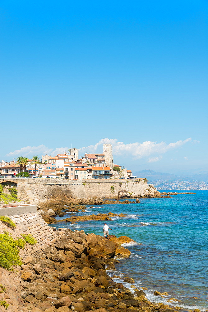 Fisherman overlooking the Old Town of Antibes, France
